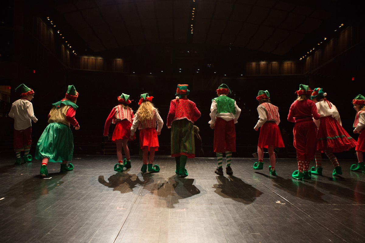 photo of Elf Jr. elves standing on stage looking out at an empty audience the day before the show