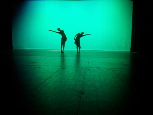Two dancers on a stage with green lighting